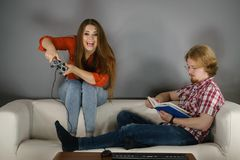 Woman playing games man reading book. Couple sitting on couch spending free time. Woman playing video games and men reading book Royalty Free Stock Images