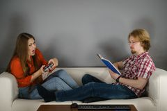Woman playing games man reading book. Couple sitting on couch spending free time. Woman playing video games and men reading book royalty free stock image