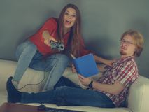 Woman playing games man reading book. Couple sitting on couch spending free time. Woman playing video games and men reading book stock image