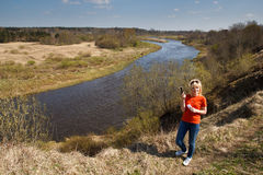 Woman playing Geocaching. A woman by a river in a unpopulated area playing Geocaching Royalty Free Stock Images