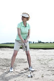 Woman playing golf at course against clear sky Royalty Free Stock Images
