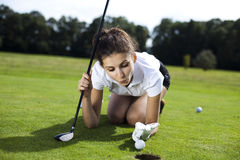 Woman playing golf on field. Girl playing golf on grass in summer Stock Photography