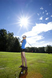 Woman playing golf on field over sun Stock Photos