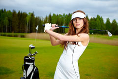 Woman playing golf on a green woman Stock Photo