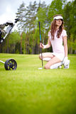 Woman playing golf on a green woman Stock Image