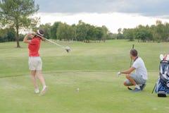 Woman playing golf husband watching shot royalty free stock photography