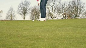 Woman playing golf lining up a putt stock video footage