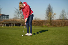 Woman playing golf lining up a putt. On the green with her golf cart and clubs visible behind on a sunny blue sky day Stock Photography