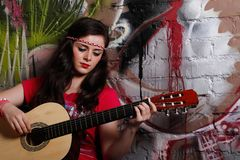 Woman playing the guitar. A young hippie woman playing the guitar in front of graffiti on a brick wall stock photos
