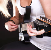 Woman playing a guitar Stock Images