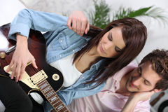 A woman playing guitar Stock Photography