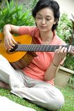 Woman playing guitar Royalty Free Stock Photos