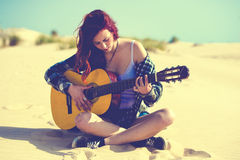 Woman playing guitar on the beach Royalty Free Stock Photography