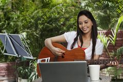 Woman playing a guitar Stock Photo