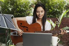 Woman playing a guitar Royalty Free Stock Photography