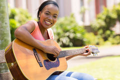 Woman playing guitar. Beautiful african american woman playing guitar outdoors Royalty Free Stock Photo