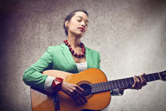 Woman playing the guitar Royalty Free Stock Images