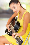 Woman playing guitar. Beautiful woman playing guitar at home Royalty Free Stock Images