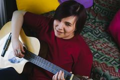 Woman playing guitar. Beautiful young woman playing guitar Royalty Free Stock Images