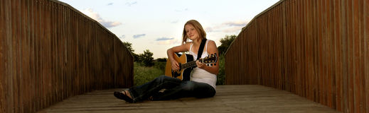 Woman playing guitar on bridge Royalty Free Stock Photos