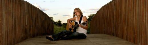 Woman playing guitar on bridge. Young woman sat on bridge playing acoustic guitar royalty free stock photos