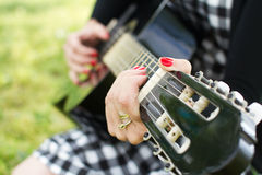 Woman playing on guitar Stock Photography