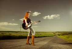 Woman playing guitar at freeway Royalty Free Stock Photography