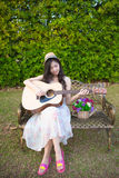 Woman playing guitar in garden Stock Photography
