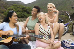Woman Playing Guitar By Happy Friends On Beach. Three cheerful women singing with female playing the guitar on the beach Royalty Free Stock Images
