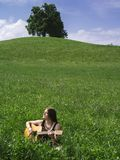 Woman playing guitar in large field Stock Image
