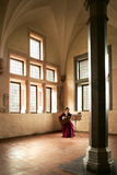 Woman playing guitar in Malbork Castle. A woman playing a guitar while sitting in a large open room in Malbork Castle, Poland Royalty Free Stock Photos