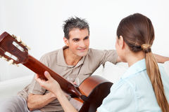 Woman playing guitar and man Royalty Free Stock Photos