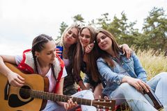Woman playing guitar nature tourism happy concept. Woman playing guitar nature tourism happy friends concept. Soulful songs. Hiking lifestyle Stock Image