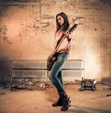 Woman playing guitar. At old dark room Stock Image