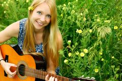 Woman Playing Guitar Outside. A young, attractive woman playing guitar outside in the grass and flowers Royalty Free Stock Images