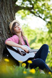 Woman playing guitar in park Royalty Free Stock Photography