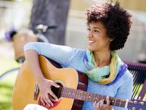 Woman playing guitar in park Stock Photography