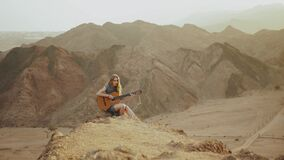 Woman playing guitar and singing in desert in sunset landscapes, desert mountains background, full hd