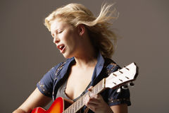 Woman Playing Guitar And Singing Royalty Free Stock Photos