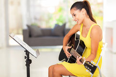 Woman playing guitar. Smiling pretty young woman playing guitar at home Stock Photography