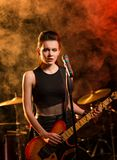 Woman playing guitar on stage. Backlit smoke on background Royalty Free Stock Photography