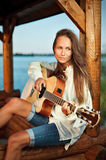 Woman playing guitar in summerhouse Stock Photo