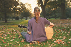 Woman playing guitar at sunset in the park Royalty Free Stock Photos