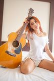 Woman playing guitar. Young beautiful asian woman playing guitar in bed room Royalty Free Stock Photos