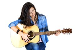 Woman playing guitar. Young woman playing guitar in studio Royalty Free Stock Images
