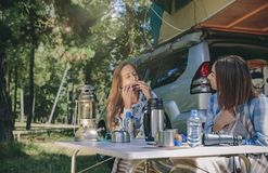Woman playing harmonica with friend in campsite. Close up of young women playing harmonica with her female friend in a campsite. Leisure time and enjoyment Stock Photo