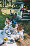 Woman playing harmonica with friend in campsite. Young women playing harmonica sitting in campsite with her female friend. Leisure time and enjoyment concept royalty free stock photography