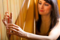 Woman playing the harp Royalty Free Stock Images