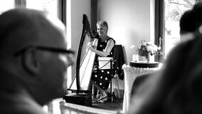 Woman Playing Harp on Stage Grayscale Stock Images