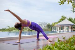 Woman playing healthy yoga beside outdoor swimming water pool. Woman playing healthy   yoga beside outdoor swimming water pool Royalty Free Stock Image